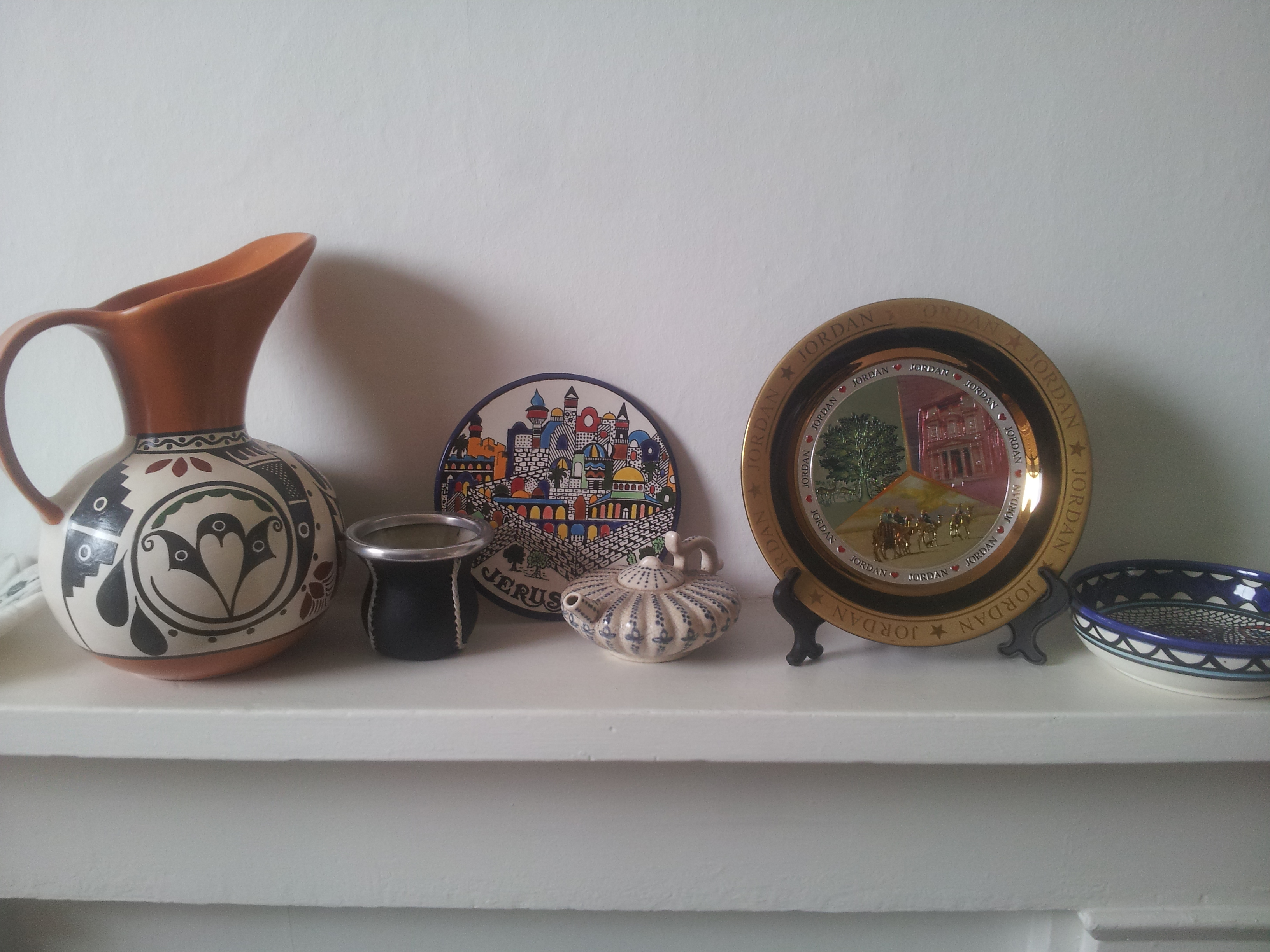 On the mantelpiece are gifts from World Voice participants including Argentine pottery and a mate cup, a plate from Jerusalem, Senegal lamp, a plate from Jordan and a Palestinian olive bowl. In the far left corner is an exquisite tile made from the same marble as the Taj Mahal.